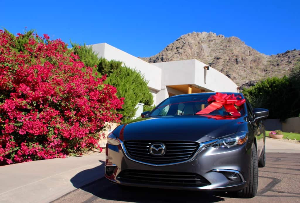 Holiday Road Trip Tips: Take a Trip, Travel Locally, silver Mazda6 with a white house and rock mountain, blue sky, giant red holiday bow