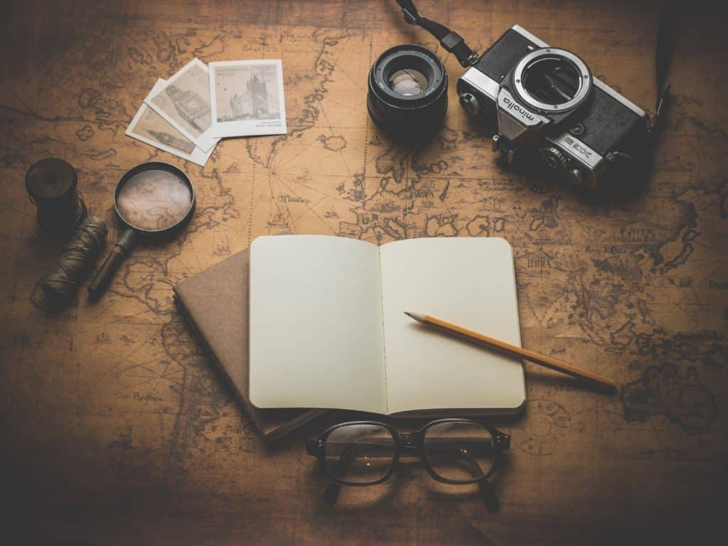 Flat lay of a book and camaera on a table,Why do people travel, #Travel