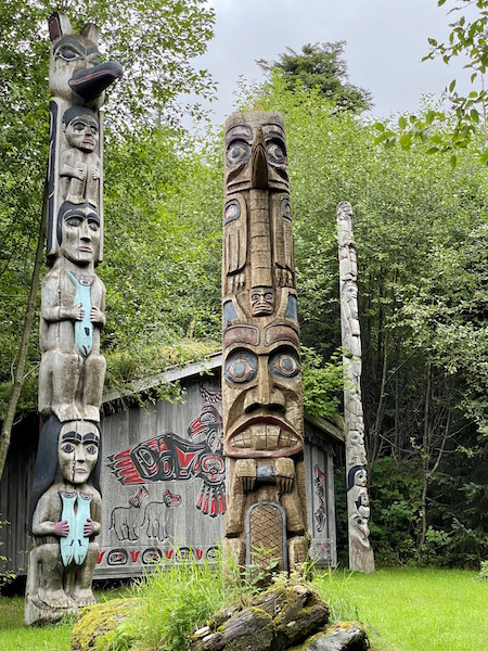 Two totem poles beside a clan house